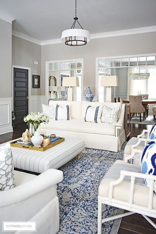 Gorgeous living room makeover reveal! New white sofas, designer pillows, new ottoman upholstery, and cream lamps create layers of refined, yet casual elegance.