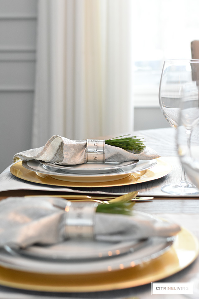 Simple and elegant Christmas table with fresh greenery and ornaments, silver and gold china and flatware.