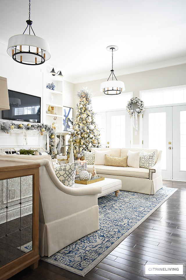 This newly updated living room is stunning, decorated for the holidays with a gorgeous flocked Christmas tree + garland, dressed in magical silver and gold!