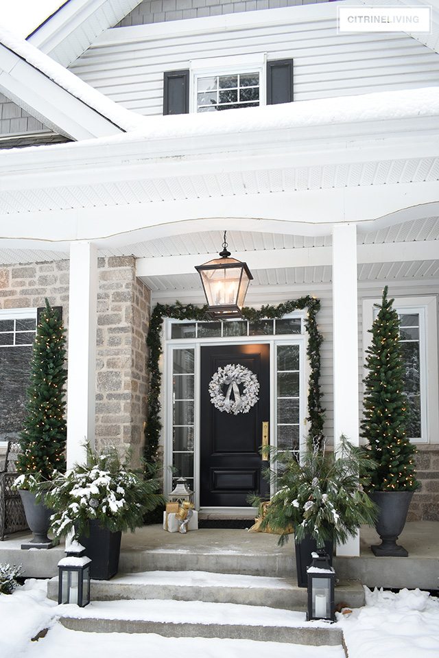 Christmas front porch decorating flocked wreath, garland, pencil trees and planters with fresh cut pine branches.