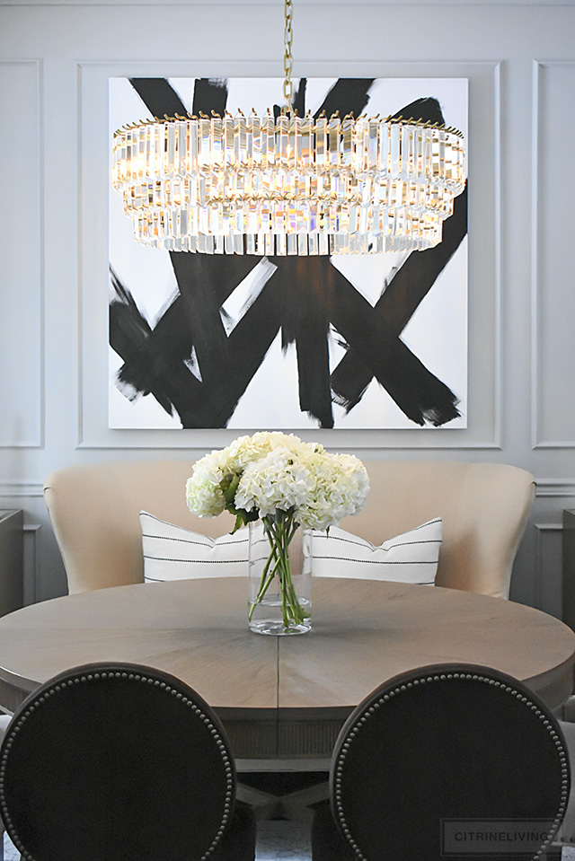 Dining room reveal with stunning crystal chandelier and dramatic black and white artwork makes a bold statement.