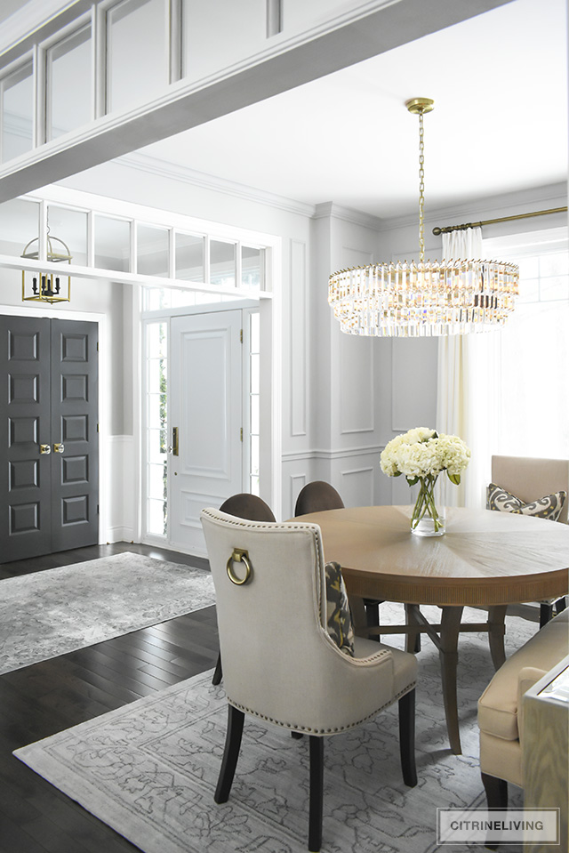 A gorgeous dining room makeover reveal with new gray walls and moldings, painted from the crown to the basboards. A spectacular chandelier sets the tone for this chic, sophisticated, bright and airy look.