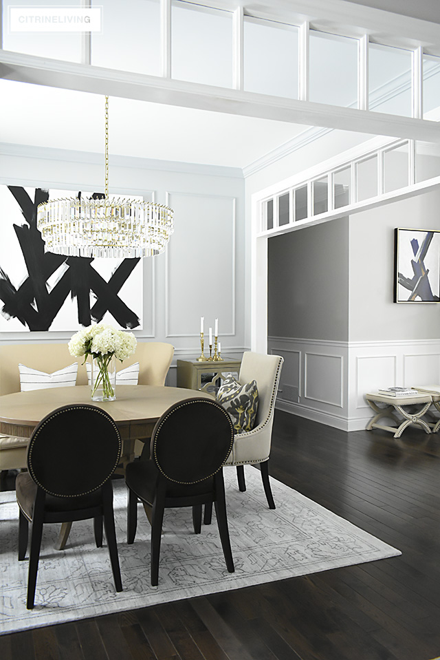 A gorgeous dining room makeover reveal with new gray walls and moldings, painted from the crown to the basboards. A spectacular chandelier sets the tone for this chic, sophisticated, bright and airy look. Dramatic black and white artwork makes a bold statement.