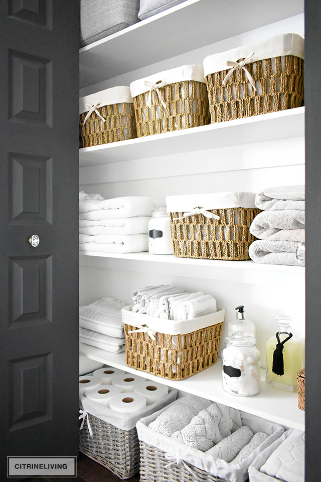 Organized linen closet reveal! A fresh coat of paint, pretty baskets and major purging, it went from messy and cramped to spacious and airy!