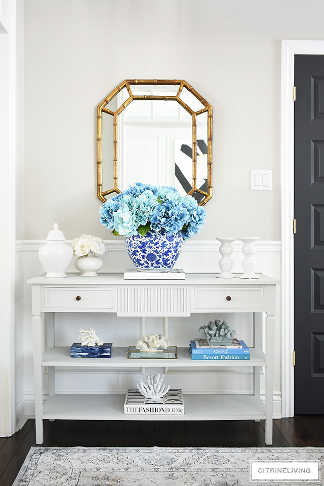 Freshen up your spring entryway decorating with a large blue hydrangea arrangement, coral sculptures, design books and white accessories.
