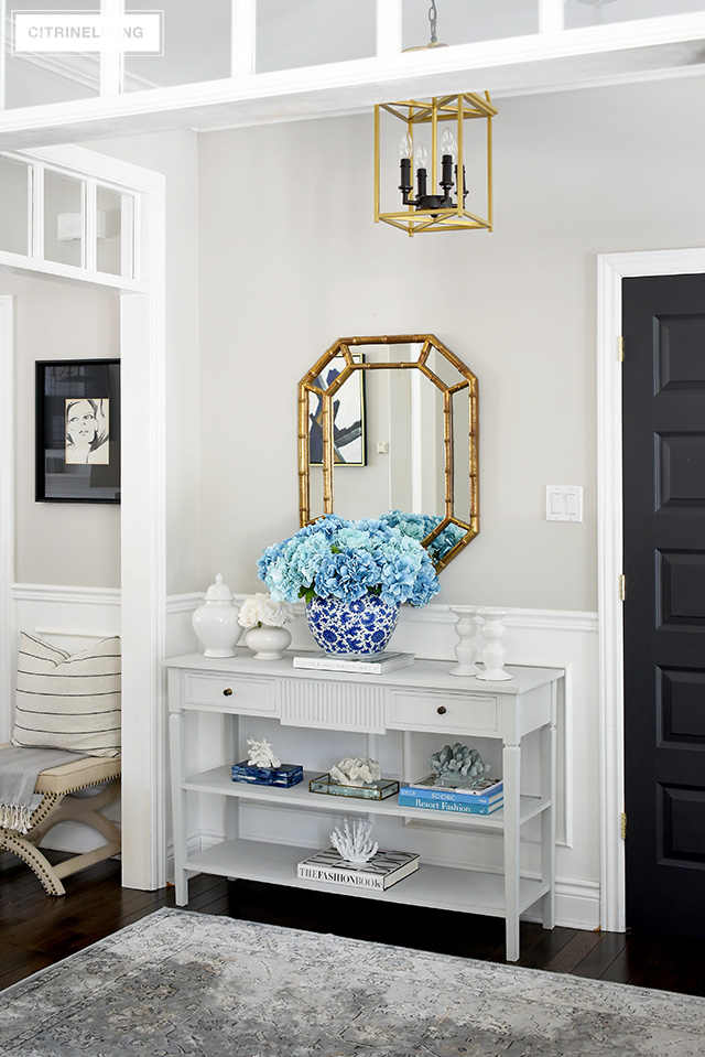 Spring entryway decorating - grey console table with oversized faux hydrangea arrangement and coral scullers create a gorgeous display!