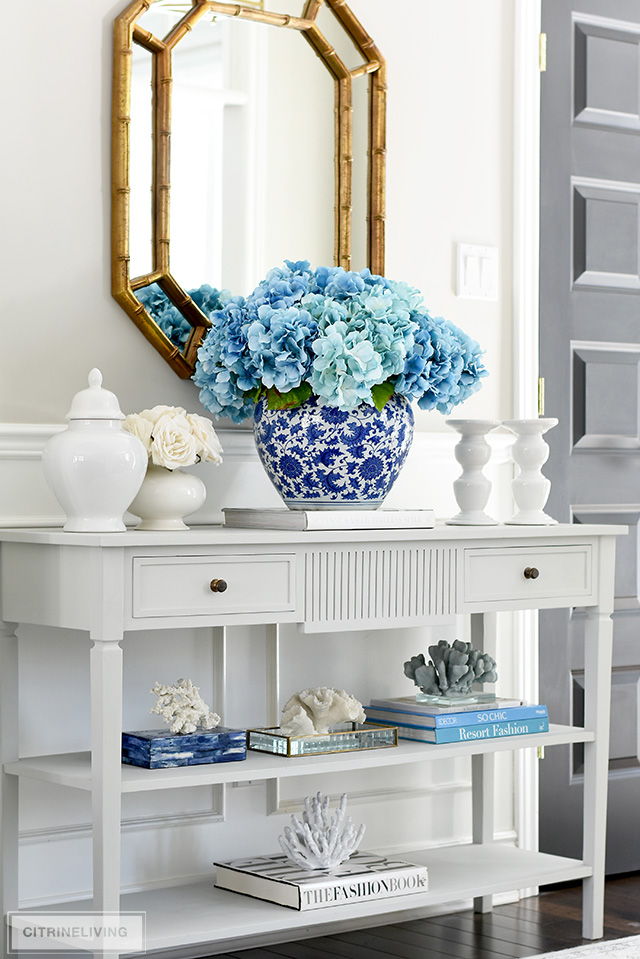 Stunning oversized faux hydrangea arrangement in a large blue and white ginger jar displayed with a gorgeous collection of coral sculptures.