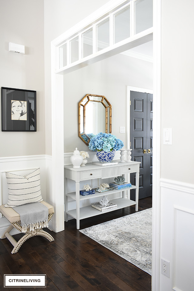 Grey console table with a beautiful display of blue and white accessories and a large-scale hydrangea arrangement makes a bold statement.