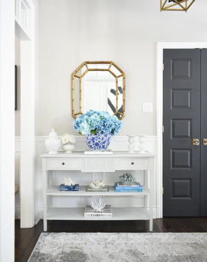 Spring entryway decorating, grey console table with large blue hydrangea arrangement in a blue and white ginger jar.