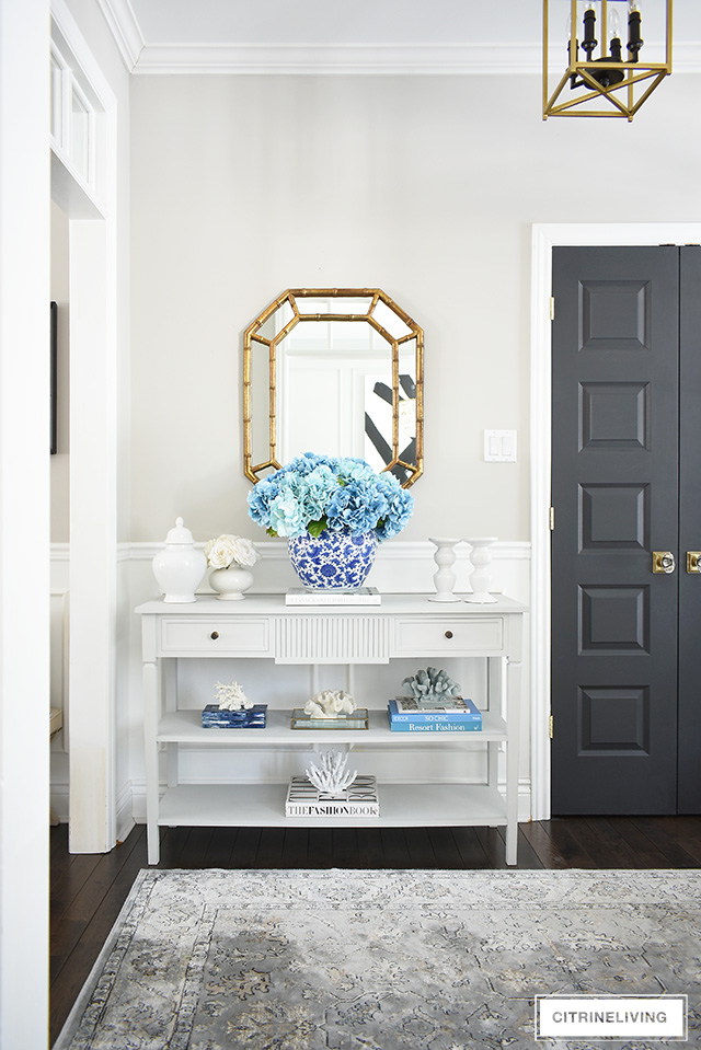 Spring entryway decorating - grey console table with oversized faux hydrangea arrangement and coral sculptures create a gorgeous display!