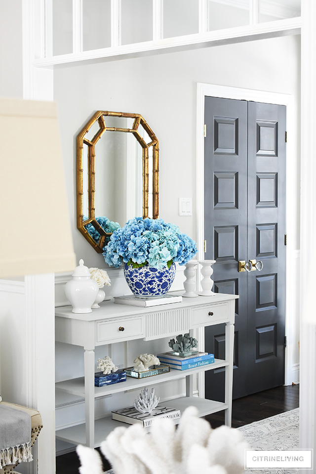 Beautiful and bold decorating with a large scale faux floral arrangement and a collection of coral.