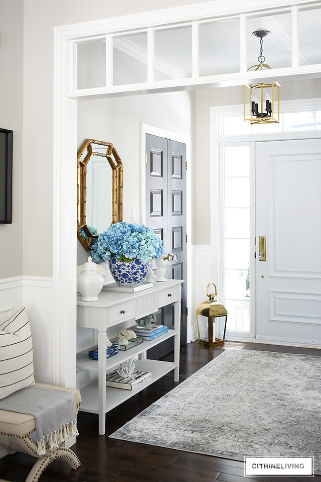 Beautiful spring decorated entryway with a large-scale faux hydrangea arrangement and coral accessories.
