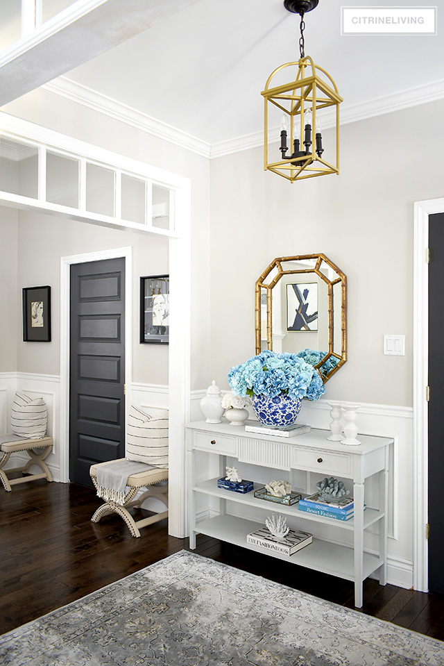 Beautiful Spring entryway decorating with a large faux hydrangea arrangement and beautiful coral sculptures.
