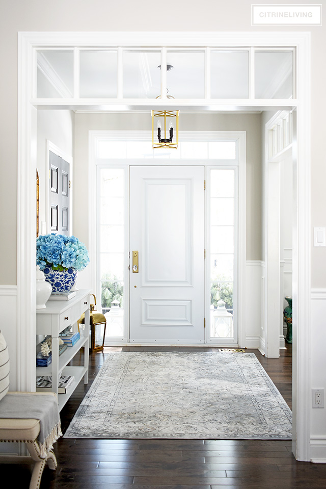 Welcoming entryway with blue, white and brass is fresh and beautiful for Spring!