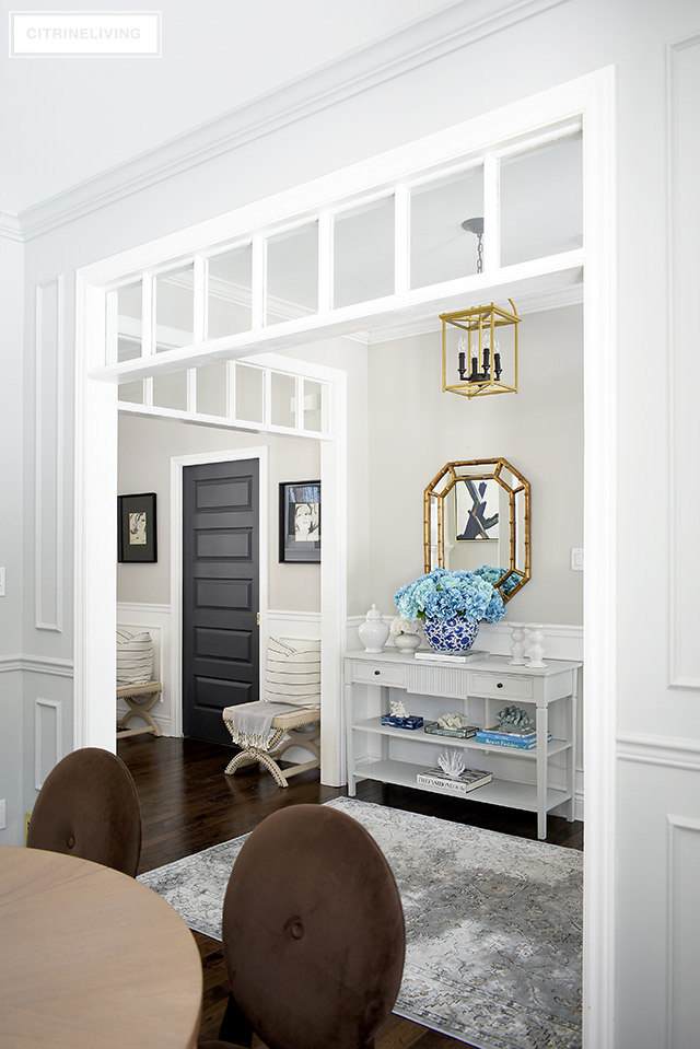reshen up your spring entryway decorating with a large blue hydrangea arrangement, coral sculptures, design books and white accessories.