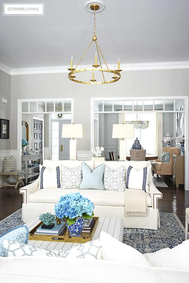 Beautiful and bright spring living room decorating in blue, white and brass plus our new gorgeous brass chandeiers and wall sconces!