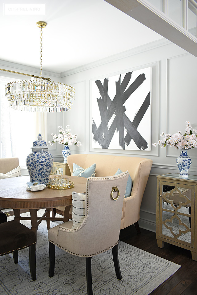 Dining room featuring modern, abstract art, grey walls, moldings, crystal chandelier. Simpler spring decorating with blue and white chinoiserie and faux cherry blossoms.