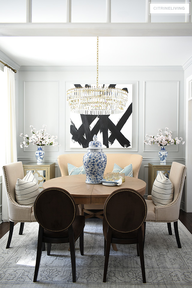 Dining room featuring transom details, modern abstract art, grey walls, moldings, crystal chandelier. Simple spring decorating with blue and white chinoiserie and faux cherry blossoms.