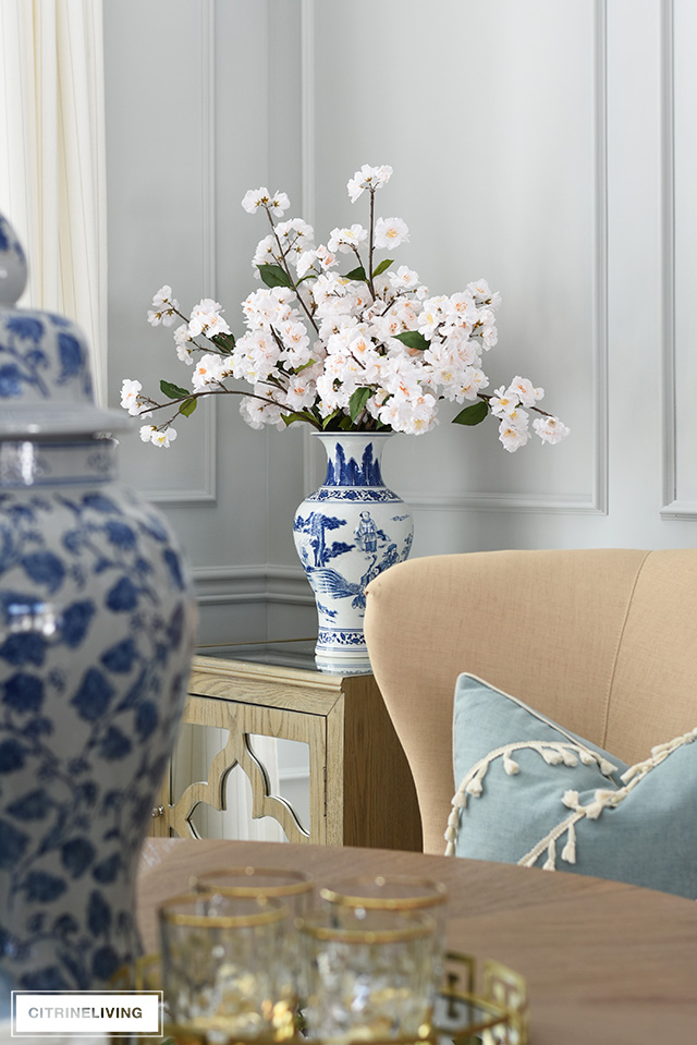 Gorgeous spring decorating with blue and white vase filled with faux cherry blossoms.