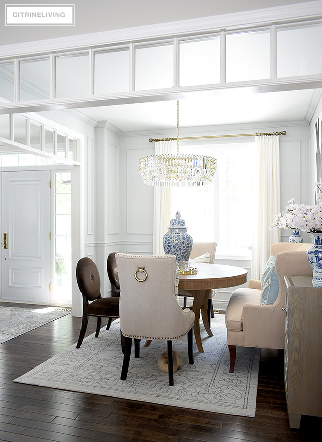 Simple spring dining room decorating using blue and white ginger jars, vases, faux cherry blossoms and light blue accessories.