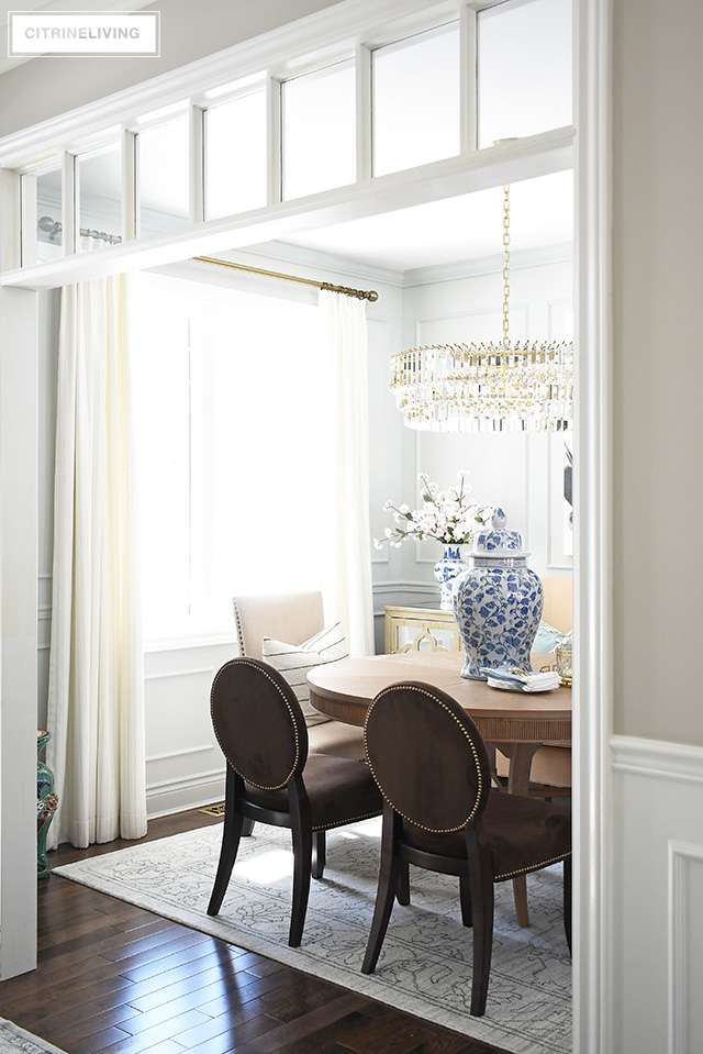 Beautiful, open concept dining room with grey walls, white drapes, crystal chandelier, vintage inspired rug. Blue and white ginger jar and cherry blossoms add a subtle spring touch.