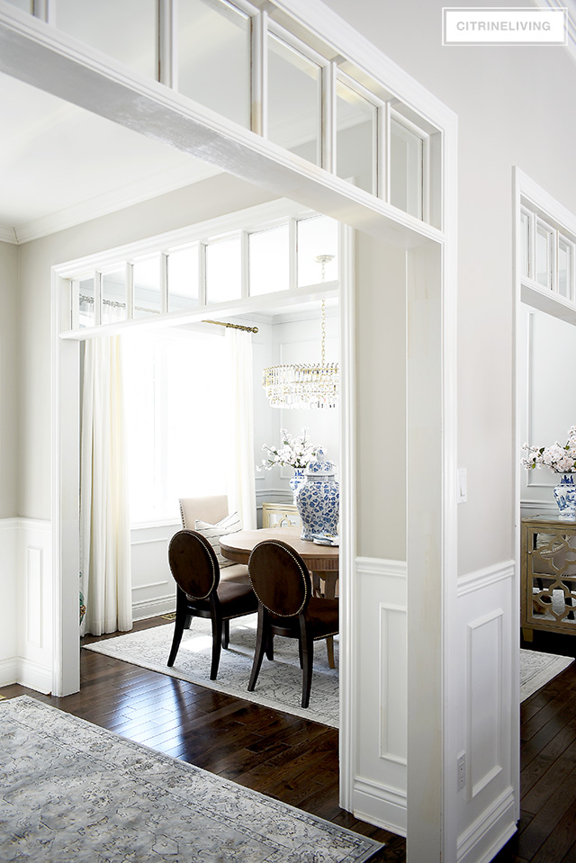 Open concept dining room with transom details on two walls. Spring decorating with faux cherry blossoms and blue and white chinoiserie.