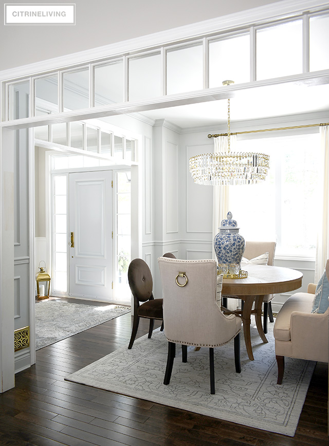 Gorgeous dining room with grey walls, moldings, crystal chandelier. Beautiful spring decor featuring blue and white chinoiserie.