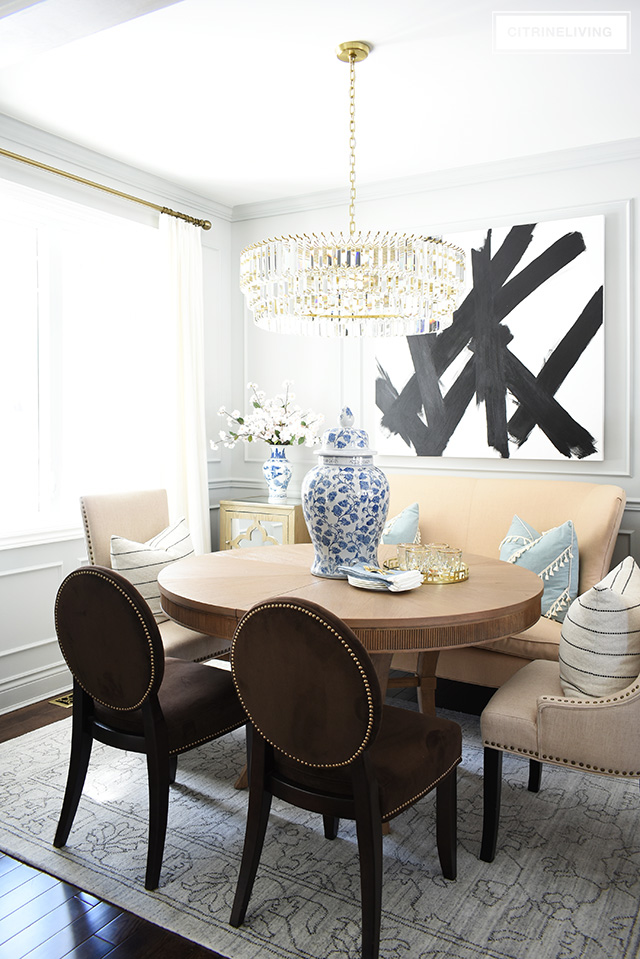 Elegant dining room with wall moldings, abstract art, crystal chandelier, white drapes and brass accents. Stonington Gray by Benjamin Moore.