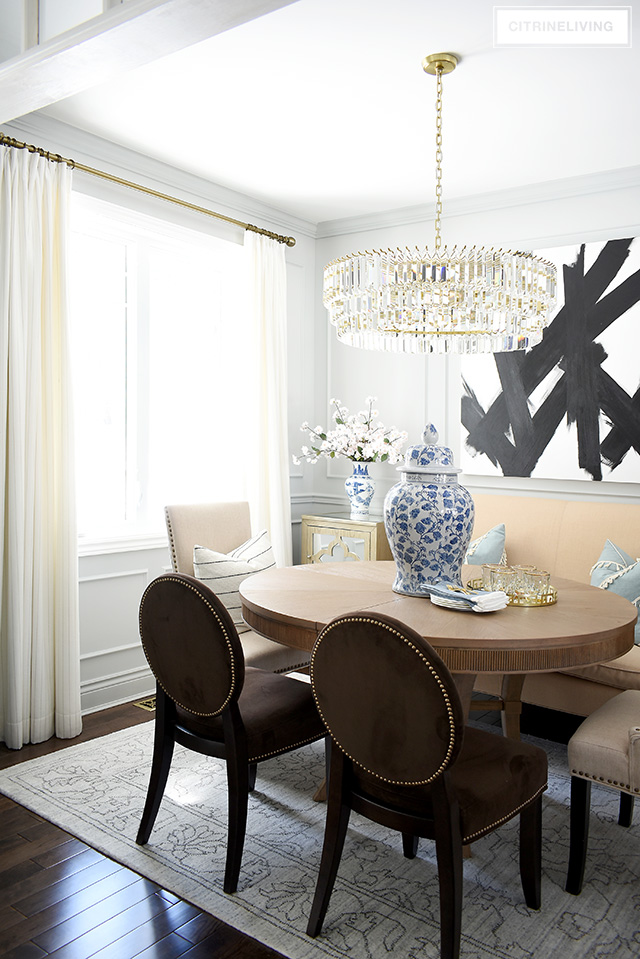 Elegant Dining Room With Wall Moldings, Abstract Art, Crystal Chandelier,  White Drapes And