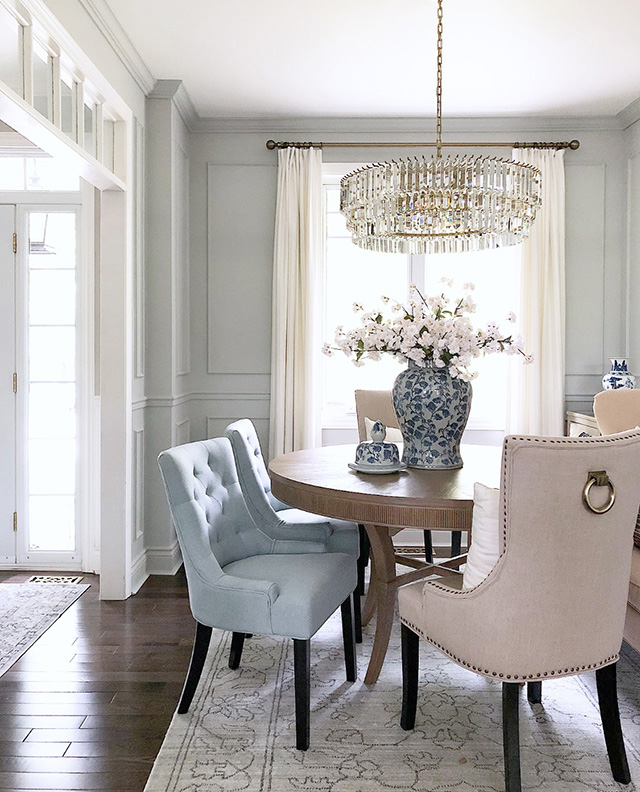 Dining room with beautiful light blue chairs, wall moldings and crystal chandelier.