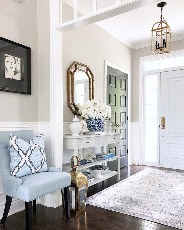 Beautiful entryway with light blue chair and console table.