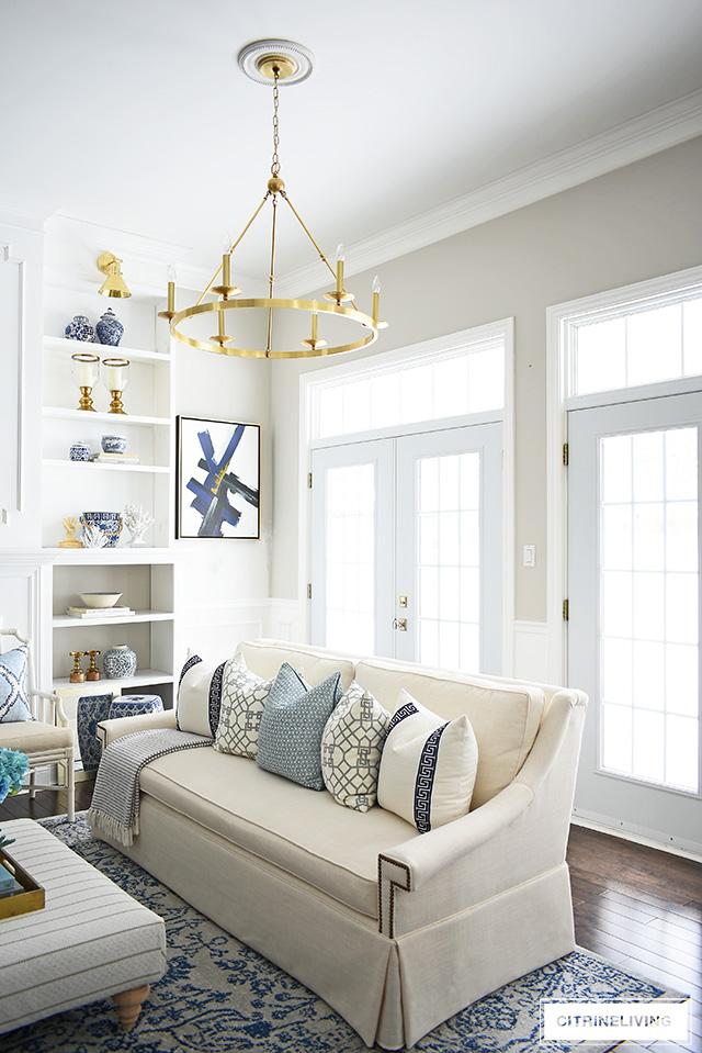 Elegant living room with skirted white sofa, vintage inspired rug and brass chandelier.
