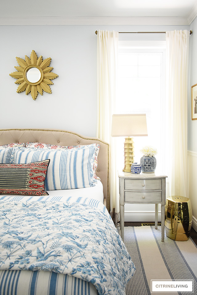 Beautiful summer decorated bedroom with blue and white striped and floral bedding , upholstered bed with brass nailhead trim is chic and elegant! Blue and white ginger jars and brass details complete this elegant bedroom.