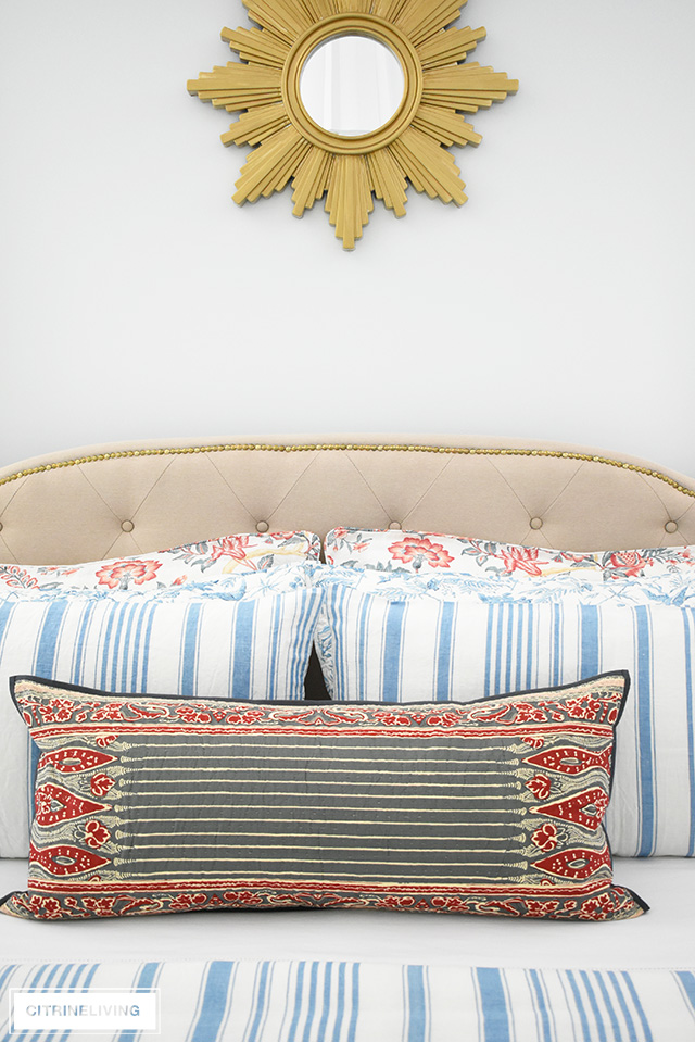 Gorgeous bedding with mixed prints, blue and white stripes and florals with mixed with red florals and block-print inspired lumbar pillow.