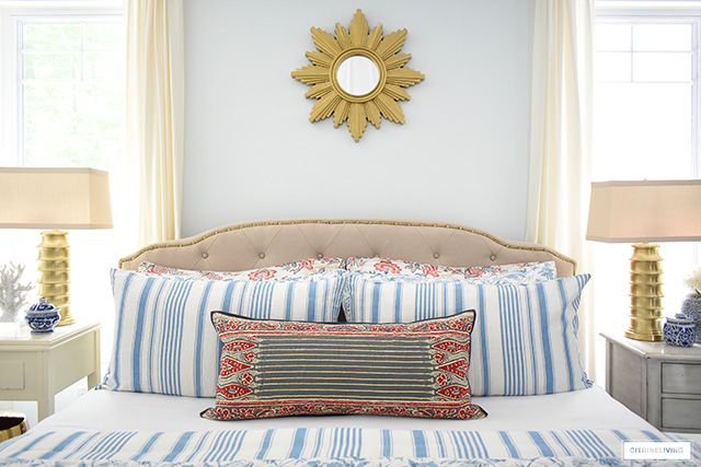 Summer bedding with mixed prints - blue and white stripes and florals with mixed with red florals and block-print inspired lumbar pillow. Gorgeous upholstered headboard with brass nailhead trim.