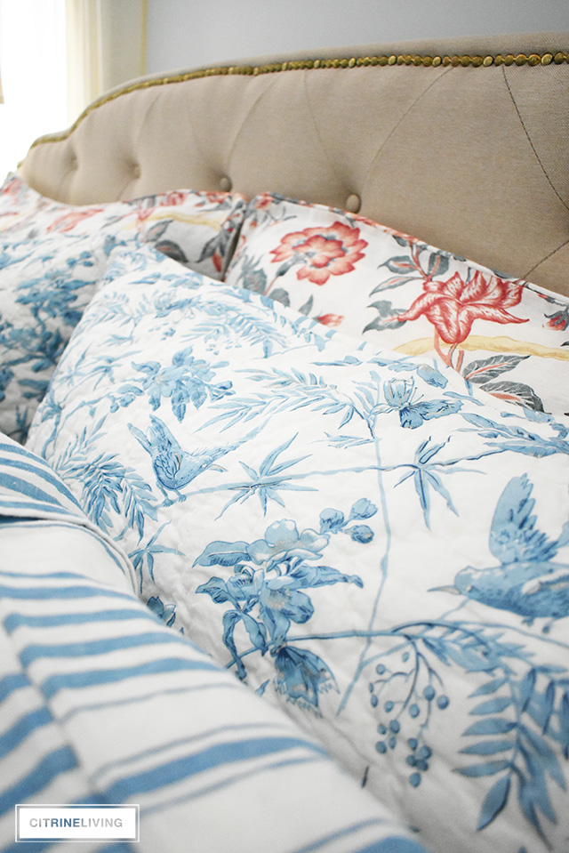 Gorgeous linen and quilted bedding with mixed prints, blue and white stripes and florals with mixed with red florals.