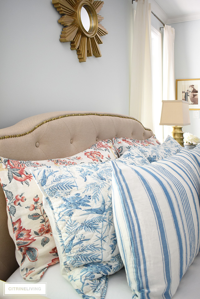 Gorgeous upholstered headboard with brass nailhead trim, layers of bedding with mixed prints in blue and white stripes and red florals.