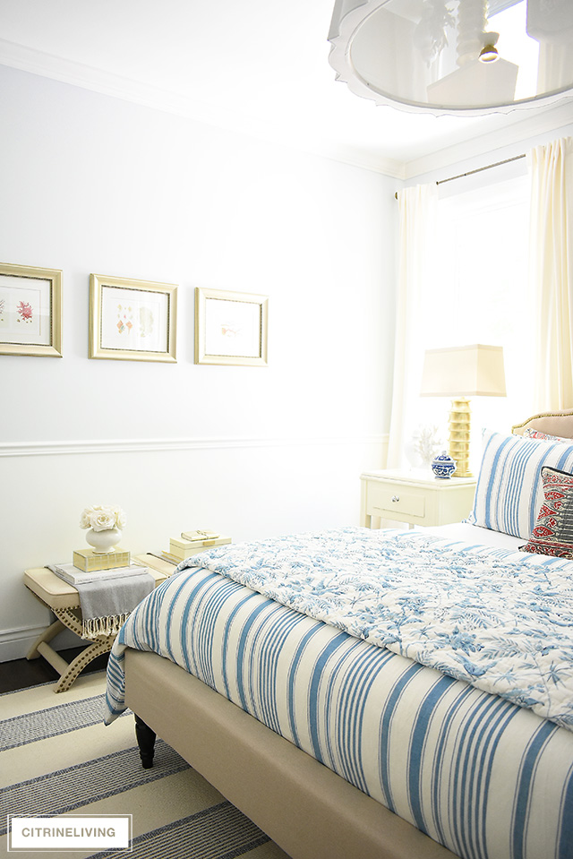 Elegant summer decorated bedroom with ivory and brass accessories, blue and white bedding.
