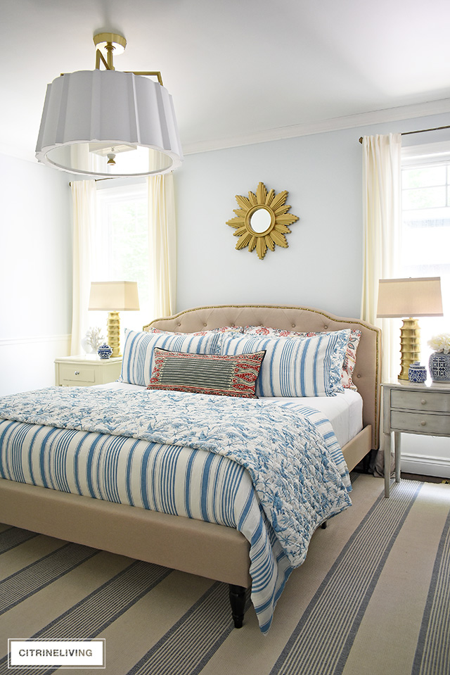 Beautiful summer decorated bedroom with blue and white striped bedding , upholstered bed with brass nailhead trim is chic and elegant. Over-scale drum shade chandelier with elegant brass detailing adds a chic and modern touch.