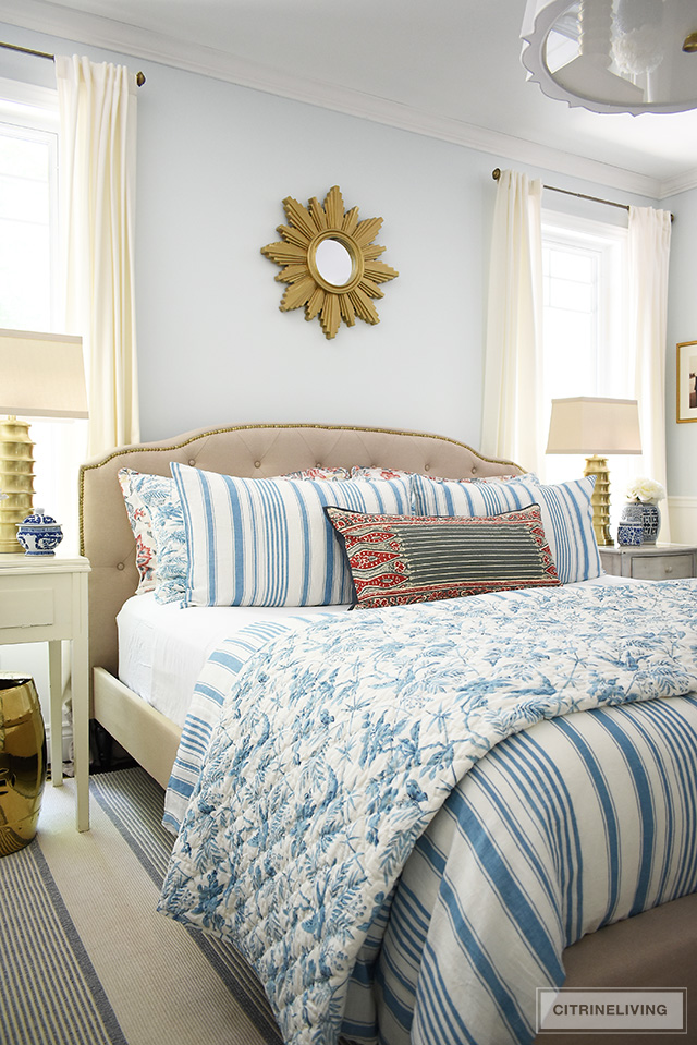 Traditional bedroom featuring a chic upholstered headboard with brass nailhead trim, brass lamps and starburst mirror. Summer bedding with a mix of blue and white stripes and red floral prints for a classic look.