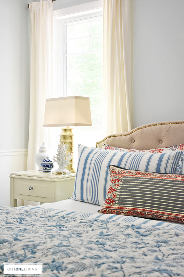 Elegant summer decorated bedroom with coastal inspired accessories, ginger jars, blue and white striped bedding.