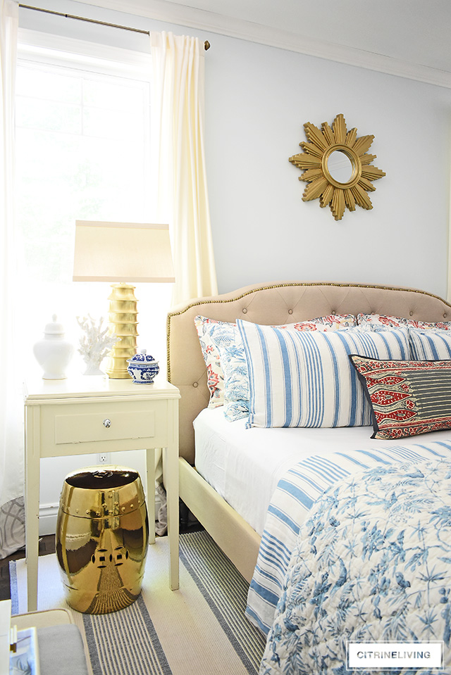 Gorgeous summer decorating in this bedroom featuring beautiful blue and white bedding mixed with red floras and block prints. Upholstered headboard with brass nailhead detail, brass lighting, starburst mirror and garden stool for a chic and elegant look.