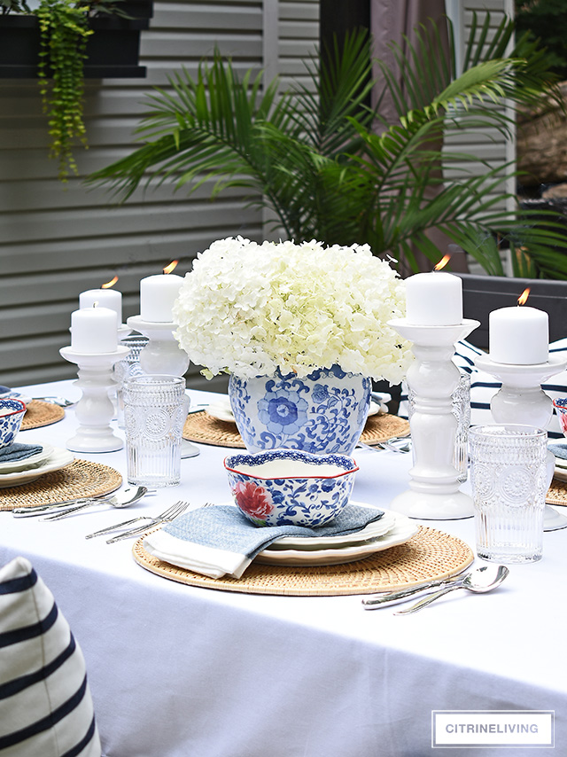 Outdoor late summer tablescape with blue and white dishes, white candleholders and fresh hydrangea arrangement.
