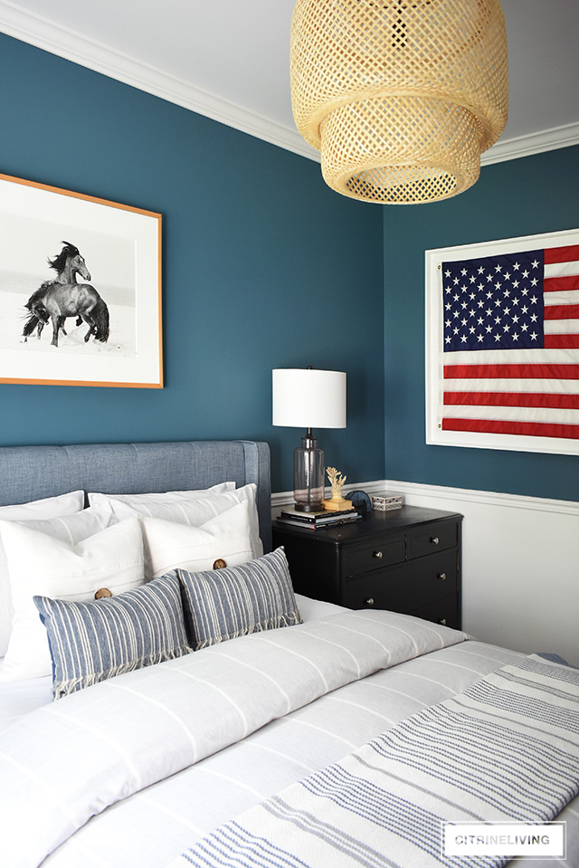 Modern coastal teen bedroom for boys - American flag, striped bedding, dark blue walls and woven elements are clean and timeless with a modern edge.