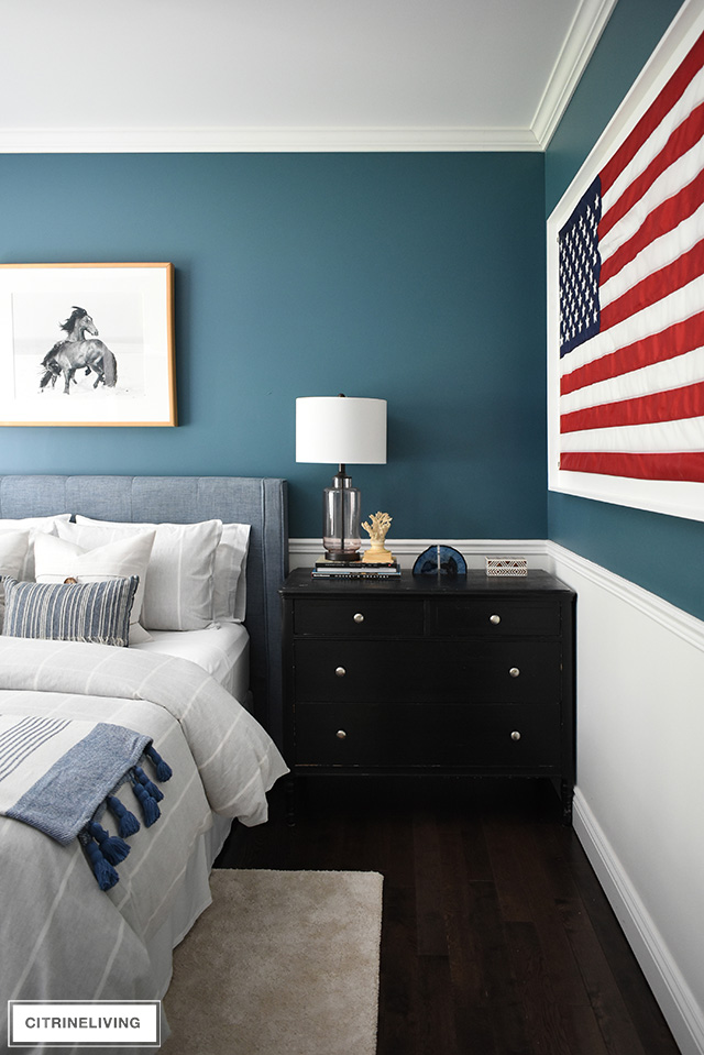 Modern coastal teen bedroom with a simple pared-back look. Striped bedding and pillows, glass lamp, framed American flag create a streamlined room with a nod to nostalgia.