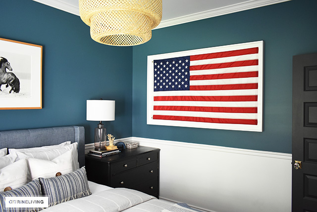 Modern coastal bedroom with American flag, striped bedding and sea-insured accessories.