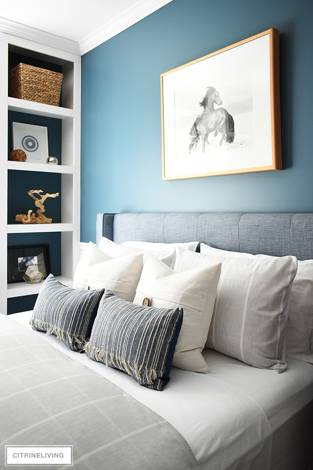 Modern coastal teen bedroom with simple striped bedding in light tones and open shelves with modern art and decor.