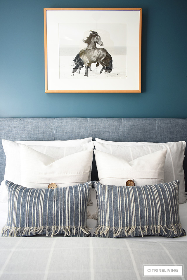 Modern coastal teen bedroom - striped and textured throw pillows paired with beach-themed horse photograph.