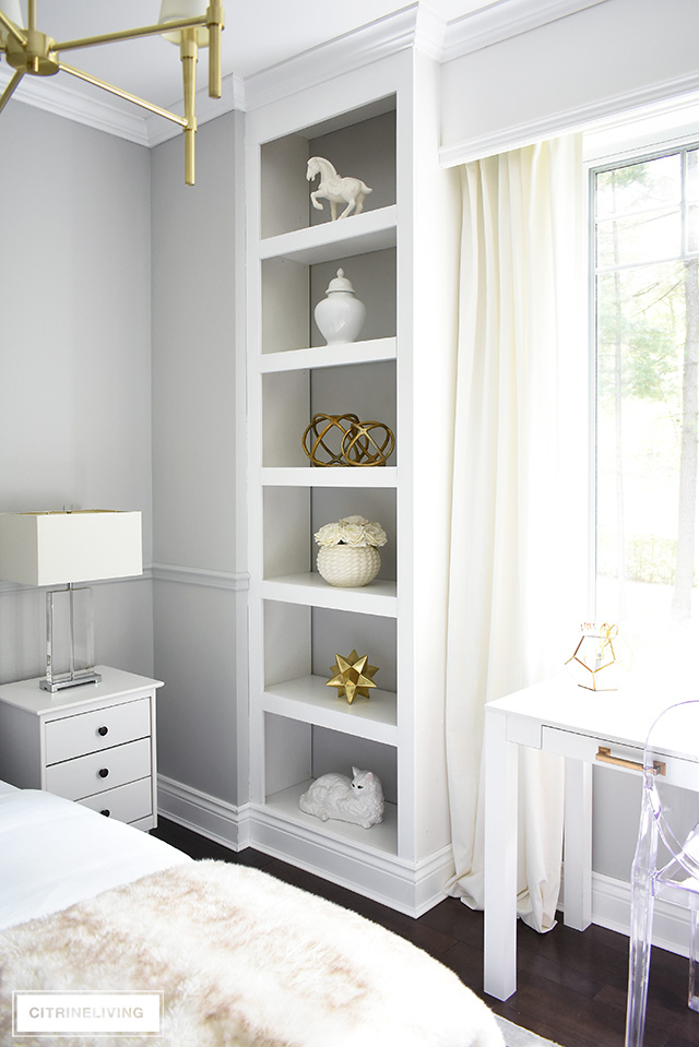 Beautiful bedroom with open built-in bookshelves, styled with simple white and brass accessories for a chic and elegant look.
