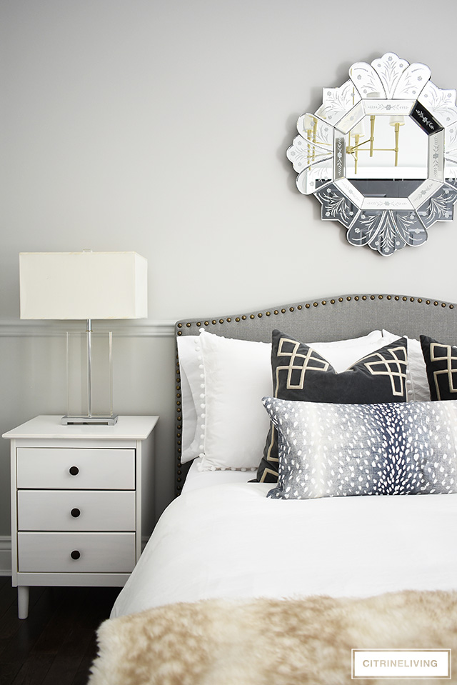Gorgeous teen girl bedroom makeover featuring a beautiful and tailored grey upholstered bed with brass nailhead trim, venetian style mirror and glam crystal table lamps.